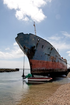 View of an old and rusty ship parked at the shoreline.