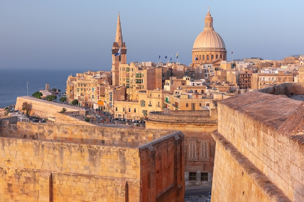 View of old town roofs, fortress, our lady of mount carmel church and st. paul's anglican pro-cathedral at sunset , valletta, capital city of malta