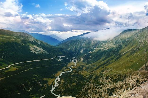 グリムゼル峠近くの曲がった道のあるアルプスの風景を見る