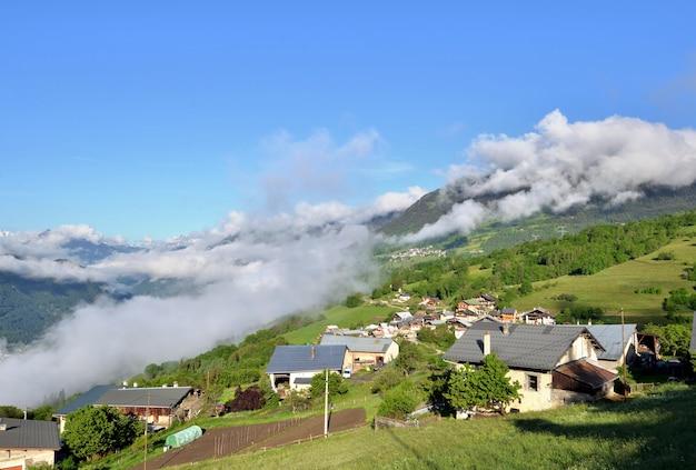 ヨーロッパの曇り空の下の丘にある高山の村の眺め