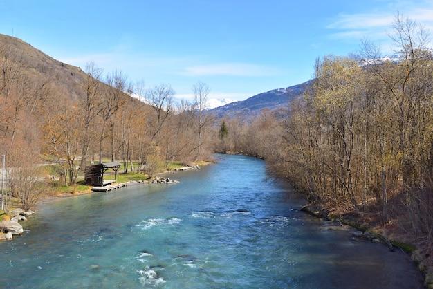 봄에 숲 은행과 눈 덮인 산 배경 사이에 흐르는 아름다운 푸른 고산 강에보기