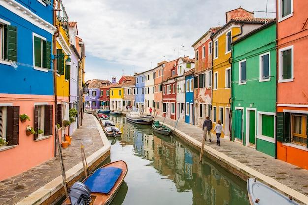 イタリア、ベニスのブラーノ島の運河に沿って反射する鮮やかな塗装の家とボートの眺め