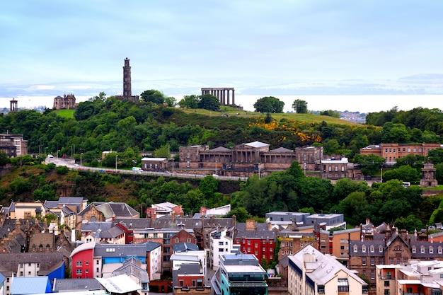 Вид на калтон-хилл и старую королевскую среднюю школу из холируд-парка, эдинбург, шотландия, великобритания