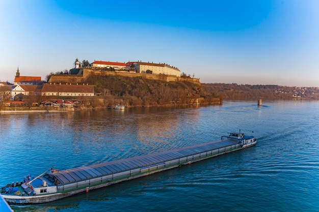 セルビア、ノヴィサドのドナウ川を越えてペトロヴァラディン要塞を通過する貨物船の眺め