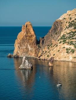 Вид на прибрежные скалы, скалы орест и пилад, мыс фиолент в балаклаве, севастополь, крым. яркий солнечный день, спокойное кристально чистое синее море.