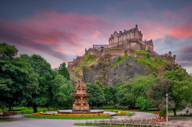Вид на эдинбургский замок со стороны садов принсес-стрит с фонтаном росс на переднем плане