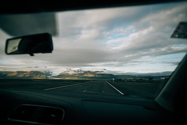 Вид на пустую исландскую дорогу изнутри автомобиля
