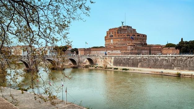 Вид на знаменитый замок святого ангела и мост через реку тибр в риме, италия