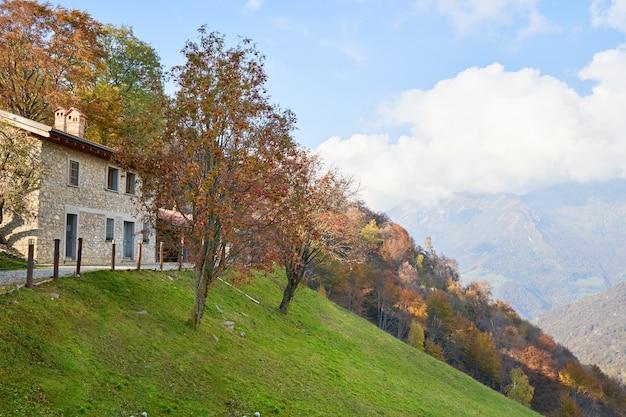 Вид на дом на склоне горы живописные альпы осенний пейзаж горные холмы в ломбардии