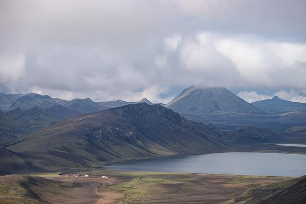Вид на горную хижину хваннгил и кемпинг с зелеными холмами, речным ручьем и озером. походная тропа лаугавегур, исландия.
