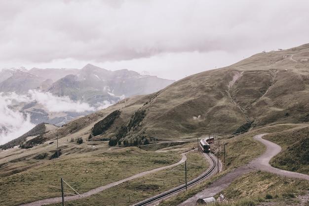 Вид на горы от станции юнгфрауйох в альпах, национальный парк лаутербруннен, швейцария, европа. летний пейзаж, дождливая погода, драматическое небо с облаками