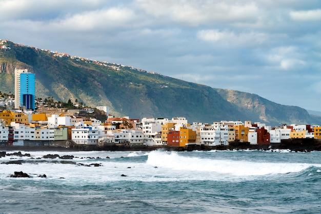 プンタブラバ、プエルトデラクルーズ、テネリフェ島、カナリア諸島、スペインの岩の上の海の海岸とカラフルな建物を見る