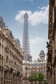 Вид на эйфелеву башню в париже между зданиями города