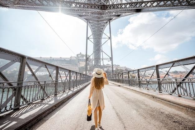 Вид на знаменитый мост луиша с женщиной, идущей в туманную и ветреную погоду в городе порту, португалия