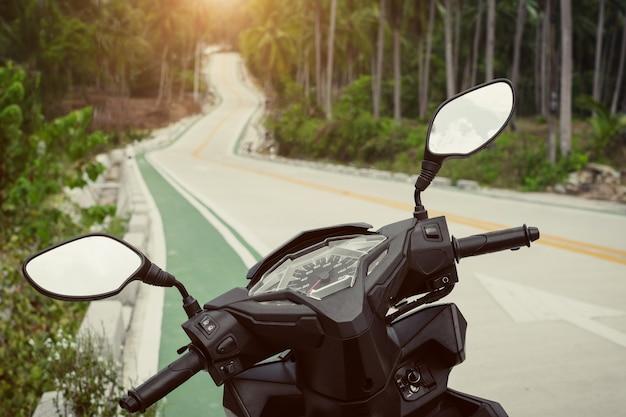 스쿠터에서 고속도로에서 볼. 열대 우림의 일몰 위의 거울과 속도계.