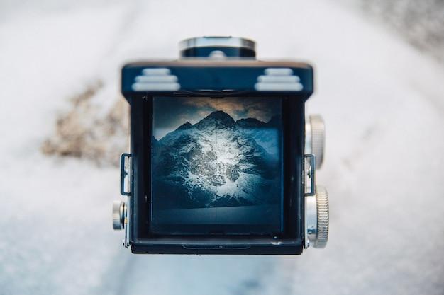 古いカメラの写真のファインダーを通して山の風景を眺める。古い学校の写真家はレトロなフィルムカメラを取ります。