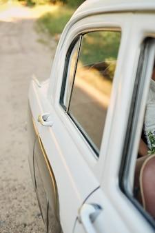 Вид на пассажирскую дверь старинного автомобиля белого цвета.