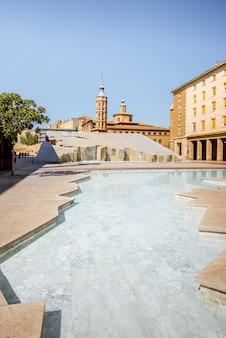 スペインの晴れた日のサラゴサ市の中心部にあるピラール広場の聖フアン教会と噴水を眺める