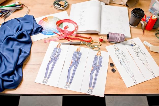 패션 그림과 재봉 도구가 있는 테이블에서 보기