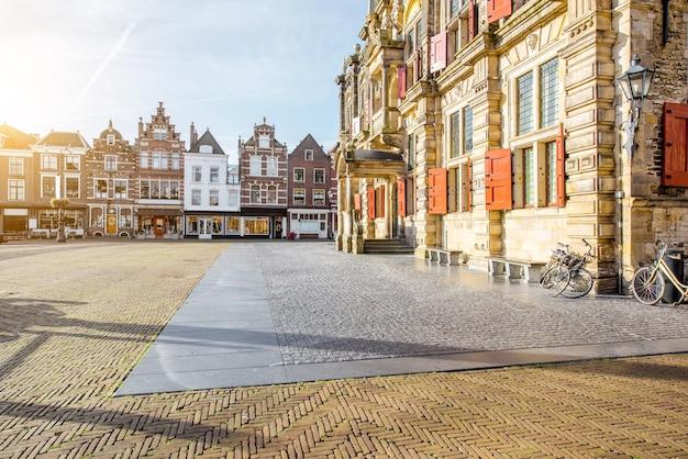 Вид на ратушу и красивые здания на центральной площади солнечным утром в городе делфт, нидерланды.