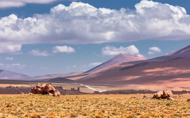 Вид на вулкан и старую лаву с драматическими облаками. потоси. боливия. южная америка