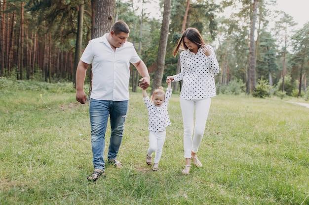 幼児を見る。母、父は森の中を歩く娘の手を握る。休暇、屋外で一緒に時間を過ごす若い家族。家族の夏休みのコンセプトです。セレクティブフォーカス