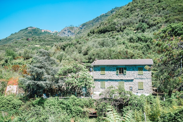 View of one old building against a majestic mountain landscape and italian vineyards in cinque terre