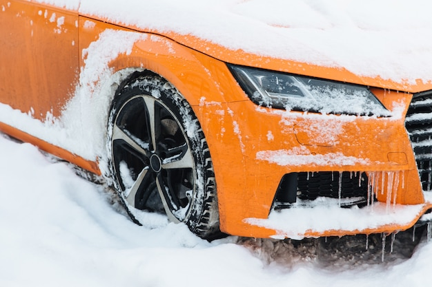 View of orange car covered with snow, stands on road, frozen on frost
