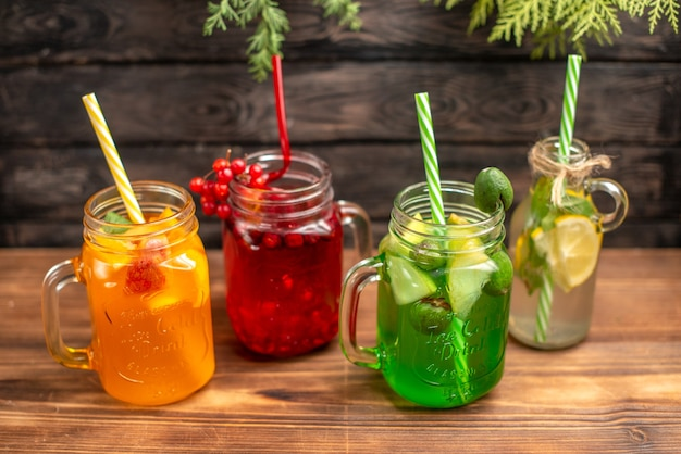 Above view of organic fresh juices in bottles served with tubes and fruits on a brown wooden background