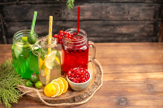 Above view of organic fresh juices in bottles served with tubes and fruits on a wooden cutting board