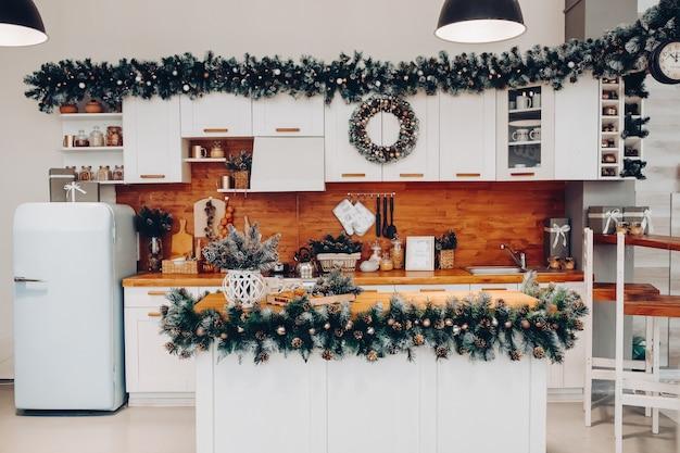 찬장과 부엌 보드 온통 크리스마스 장식과 함께 아름다운 흰색 부엌을 봅니다. 찬장에 크리스마스 화환이 있습니다. 소나무 콘과 함께 자연 전나무 나무 가지입니다.