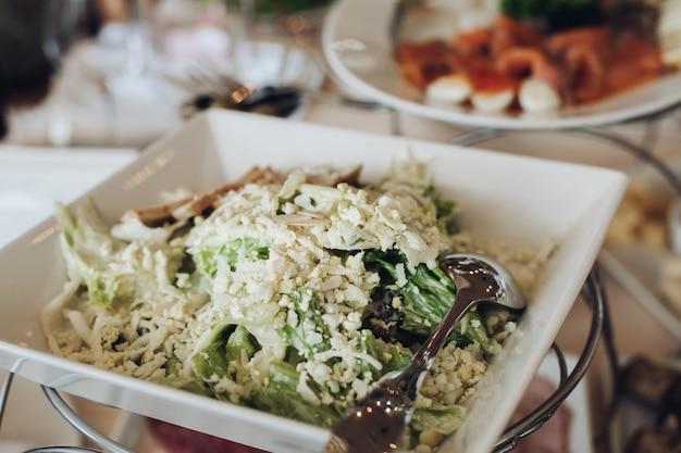 結婚式のテーブルで提供されるおいしい料理をご覧ください。サラダと前菜、食器と調理器具。
