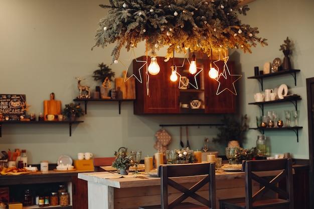 축제 별과 전나무 나무 가지로 장식 조명 아래에서 겨울 크리스마스 저녁 식사를 위해 식탁 위에 제공됩니다. 크리스마스 저녁 식사 개념입니다.