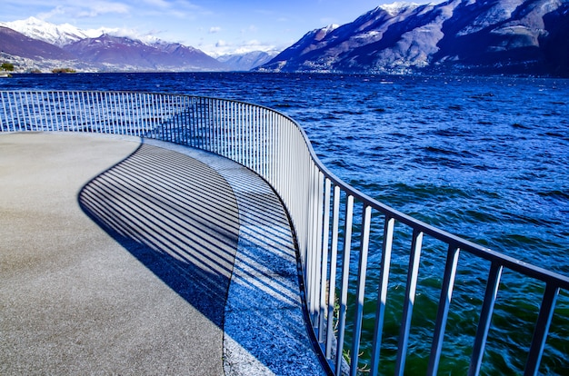 Вид на альпийское озеро маджоре с заснеженной горой в тичино, швейцария