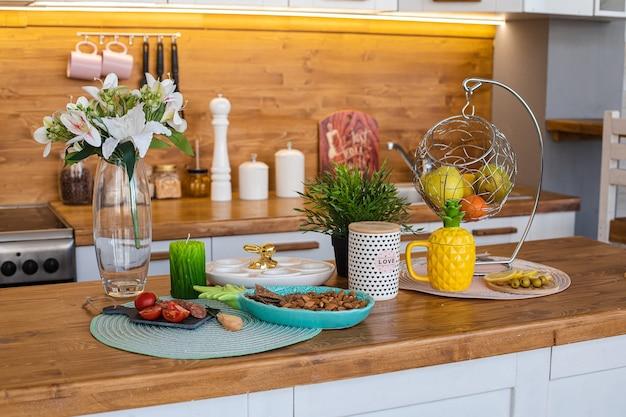 Вид на деревянную стойку с закусками, цветами лилии, свежими фруктами в корзине, чайником и яичной тарелкой для празднования пасхи.