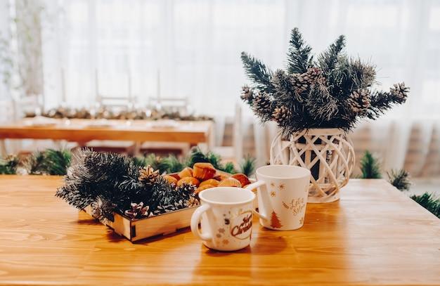 Вид на деревянный стол с двумя фарфоровыми чашками, деревянный поднос с вкусными домашними кексами и еловые ветки в вазе.