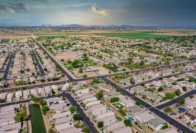 アリゾナ州フェニックスの近くにある険しい山々のエイボンデール市の砂漠の小さな町を見下ろす景色