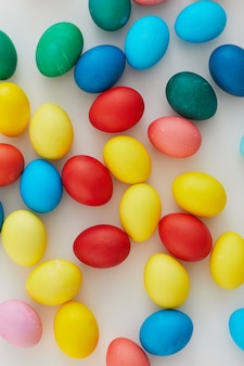 Above view of pastel colored easter eggs arraigned in minimal composition on white background, copy space