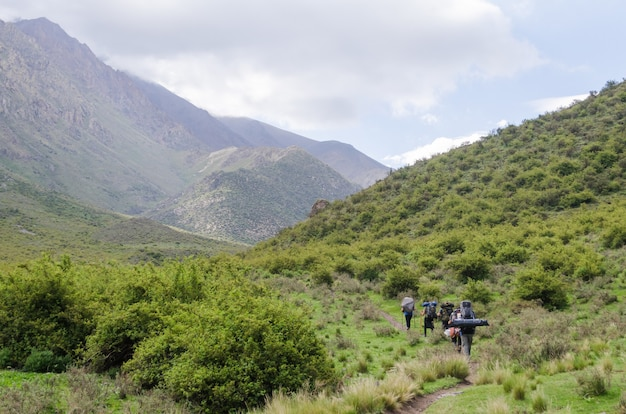 View of people trekking in andes mountain, argentina with a cloudy sky in the background