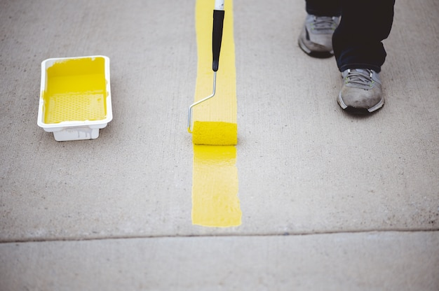 View of a person repainting the parking lines of the asphalt of a parking lot with yellow paint