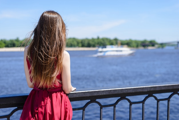 Behind view photo of woman in red dress looking at ship and nature