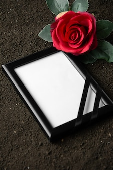 Above view of picture frame with red flower on dark soil grim reaper death funeral portrait