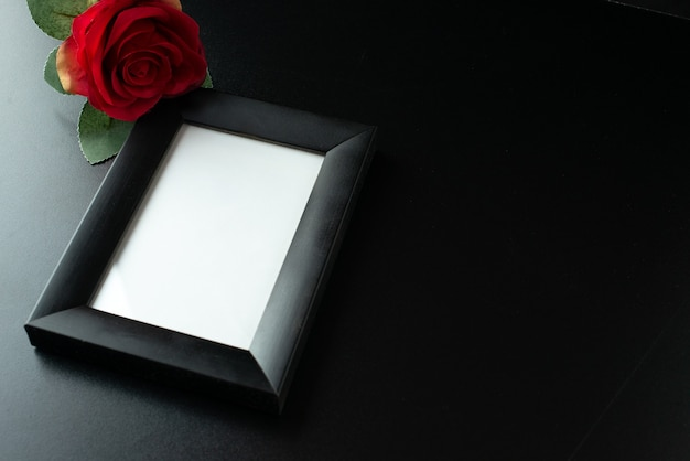Above view of picture frame with red rose on dark surface