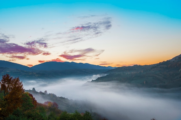 View of picturesque mountain valley with blue sky on background. magnificent highlands with colorful trees and hills covered with dense fog. concept of nature and rolling hills.