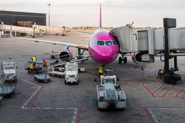 View of a pink airplane getting ready for takeoff on the airport of barcelona, spain.