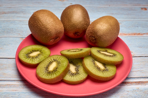 View of a pink plate with slices of kiwi and whole kiwis