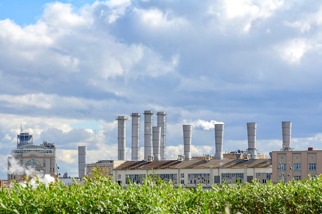 View of the pipes of the plant from which there is white smoke against the sky.