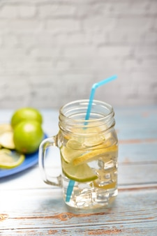View of a pitcher of lemonade with ice next to some slices of lemon and lime