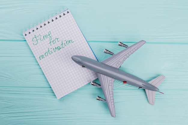 Above view of plastic toy passenger jet plane and notepad near it. turquoise wooden background.