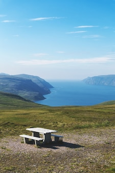 View point with a table and benches on the background of mountains and sea